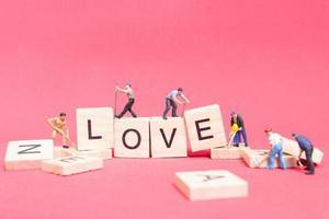Travailleurs miniatures construisant le mot amour sur des blocs de bois avec un fond rose, concept de la Saint-Valentin photo