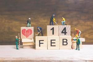 Travailleurs miniatures construisant les mots et les dates de la Saint-Valentin sur des blocs de bois avec fond en bois, concept de la Saint-Valentin photo