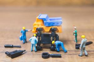 Travailleurs miniatures réparant une roue d'un camion sur un fond de bois