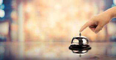 Bell sur un comptoir pour le service avec une main sur un arrière-plan flou photo