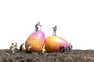 Les gens miniatures travaillant sur les oeufs de Pâques pour le jour de Pâques avec un fond blanc photo