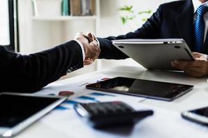 deux personnes se serrent la main sur des papiers de tableaux et de graphiques à côté de tablettes photo