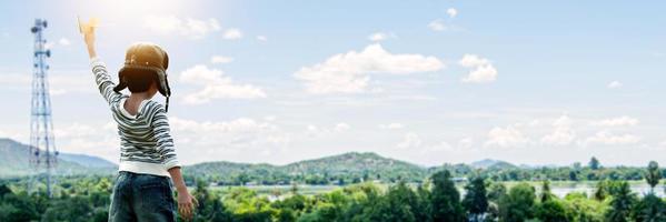 Garçon en casque tenant un avion en papier regardant le paysage d'arbres, de montagnes et de ciel bleu nuageux photo