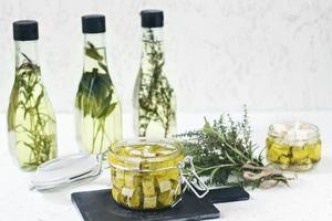 Feta marinée dans un bocal en verre, épices et huile d'olive aromatisée sur un fond en bois photo