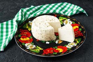 Fromage blanc sur une assiette sur fond noir et serviette photo
