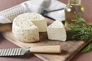 Fromage blanc sur une planche de bois avec de l'huile d'olive sur fond brun photo