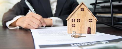 personne qui signe le contrat à côté de la maison modèle et des clés photo