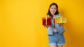 Femme asiatique souriant et tenant des coffrets cadeaux rouges et or sur fond jaune photo