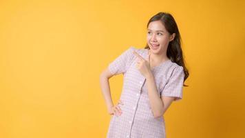 Femme asiatique souriant et faisant des gestes vers l'espace de copie sur fond jaune