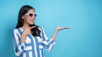 Femme asiatique avec des lunettes de soleil blanches faisant des gestes vers l'espace copie sur fond bleu photo