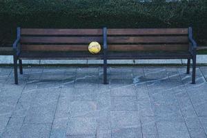 ballon de football sur un banc en bois dans la rue photo