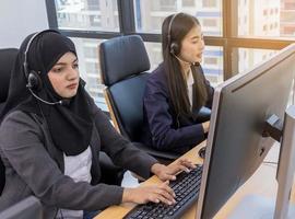 Les jeunes femmes musulmanes asiatiques travaillant au bureau sur l'ordinateur photo