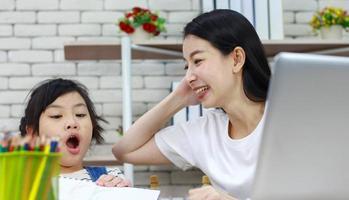 Mère asiatique est assise avec bonheur en enseignant à sa fille la lecture des devoirs photo