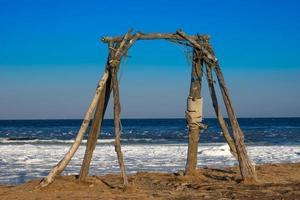 balançoire en bois sur une plage avec la mer en arrière-plan photo