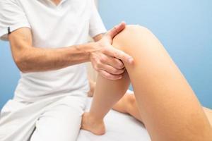 Un physiothérapeute effectue un test du tiroir du genou à une femme photo
