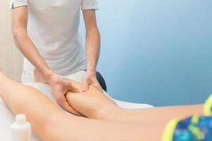 massage des mollets par un physiothérapeute professionnel photo