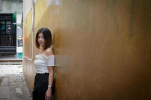 femme posant contre un mur dans une ruelle photo