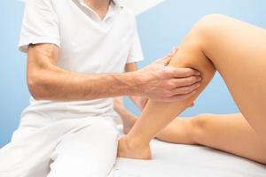 massage délicat des mollets dans l'atelier d'un physiothérapeute professionnel photo