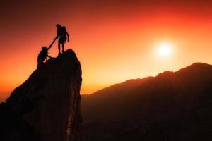 équipe de grimpeurs aide à conquérir le sommet photo
