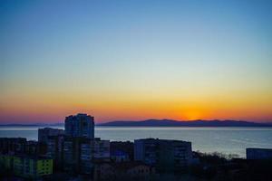 Paysage urbain à côté de plan d'eau avec coucher de soleil coloré à Vladivostok, Russie photo