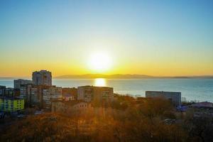 Paysage urbain à côté d'un plan d'eau avec coucher de soleil coloré à Vladivostok, Russie photo