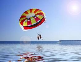 Les gens parachute ascensionnel sur un plan d'eau avec un ciel bleu clair