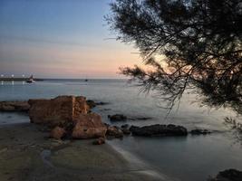 Plage méditerranéenne sans personnes au coucher du soleil à calpe, alicante photo