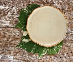 Vue de dessus d'une assiette en céramique vide avec des feuilles sur un fond de table en bois photo