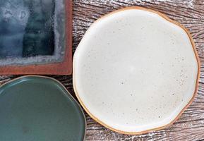 Vue de dessus des assiettes en céramique vides sur un fond de table en bois photo