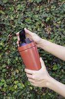 Mug thermos en aluminium dans les mains avec fond de mur de feuilles vertes