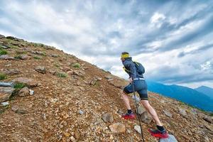 Athlète skyrunner lors de l'entraînement dans les montagnes avec des bâtons photo