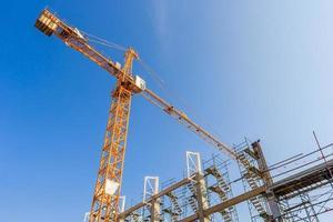 Grues de construction industrielle et bâtiment dans un beau fond de ciel bleu photo