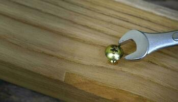 Gros plan d'une clé vissant un écrou dans une planche en bois, à défaut d'utiliser le bon concept d'outil