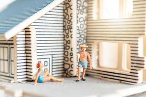 personnes miniatures restant à la maison faisant l'auto-quarantaine pour éviter le coronavirus, rester à la maison
