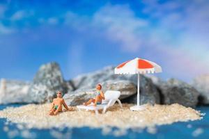 personnes miniatures portant des maillots de bain se détendre sur la plage avec un fond bleu, concept de l'été