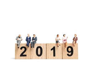 Gens miniatures assis sur le numéro de bloc en bois 2019