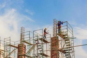 les travailleurs de la construction travaillant sur des échafaudages à un niveau élevé par des normes de sécurité définies photo