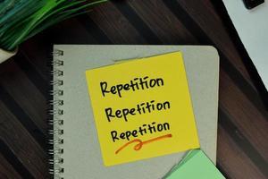 Répétition, répétition, répétition écrite sur pense-bête isolé sur table en bois