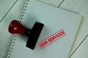 Tampon en caoutchouc poignée rouge et nos services texte isolé sur table photo