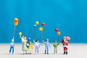 Père Noël miniature et enfants tenant des ballons, joyeux Noël et bonne année concept