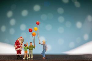 Père Noël miniature et enfants tenant des ballons, joyeux Noël et bonne année concept photo