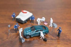 police miniature et détective debout autour d'une voiture, concept d'enquête sur les lieux du crime photo