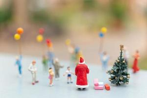 Père Noël miniature tenant des cadeaux pour une famille heureuse, Noël et bonne année concept