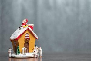 Les gens miniatures peignant une maison et le père Noël assis sur le toit, joyeux Noël et bonnes vacances concept photo
