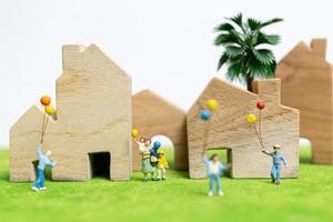 Famille miniature marchant dans un champ avec des ballons, des relations familiales heureuses et un concept de temps libre photo