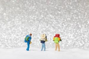 Backpackers miniatures marchant sur un fond de neige, concept d'hiver photo