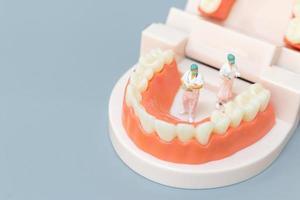 Dentiste miniature réparant les dents humaines avec les gencives et l'émail, la santé et le concept médical