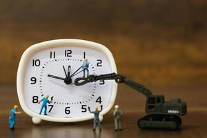 équipe miniature travaillant sur un réveil, concept de temps de travail photo