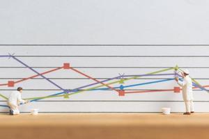 Travailleur miniature peinture des graphiques d'entreprise sur fond blanc, concept de croissance d'entreprise photo
