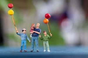 famille miniature tenant des ballons dans le parc, concept de la journée mondiale des enfants photo